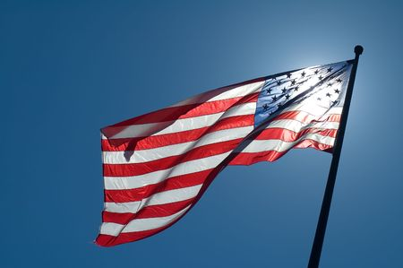 back lighted american flag, clear blue sky photo