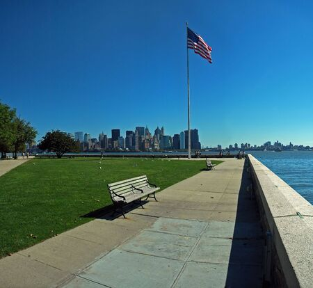 american flag and lower manhattan in background, photo taken from ellis island photo