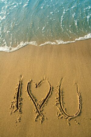 I love you written in sand on a beach, water in cyan color