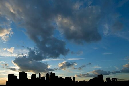 lower manhattan black silhouettes, dark vivid clouds in background,  photo