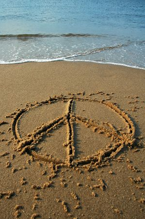 peace sign written in sand on a beach, cyan water in background Stock Photo