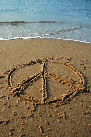 symbol peace: signo de la paz escritos en la arena en una playa, el agua en el fondo cian