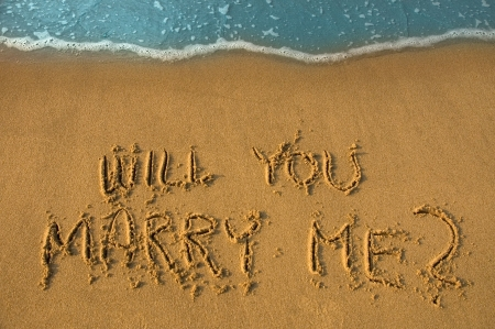 proposals: will you marry me written in sand, cyan water Stock Photo