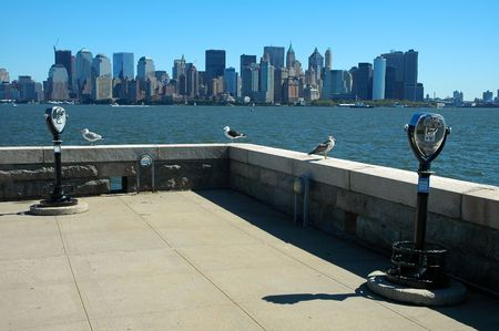 view from ellis island, three sea gulls and two binoculars in foreground, lower manhattan in background photo