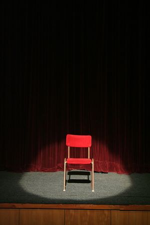 red chair on theatre stage lighted with spotlight, red curtain in background Stock Photo
