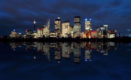 sydney cbd panorama at night, buildings reflection in water, dark cloudy night sky Stock Photo