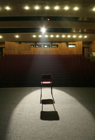 lighted: red chair on brown stage lighted with a spotlight, empty seats in background