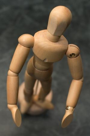 wooden figure conceptual gesture, distance blur, dark marble background photo