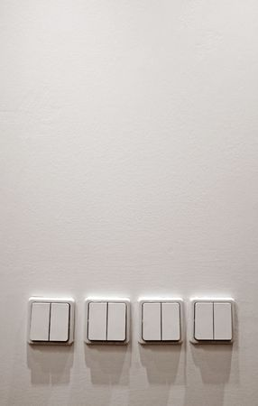 white wall with four plastic light switches,  photo