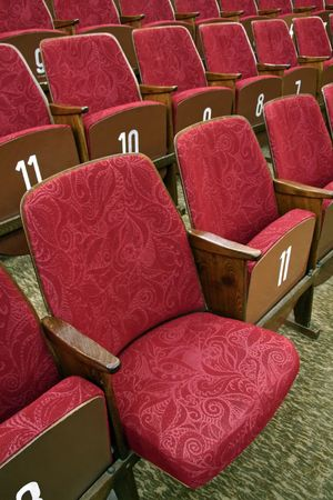 red theatre seats with white numbers, one seat unfolded