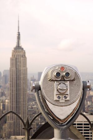 view from rockefeller center, binoculars in foreground, empire state building in background, distance blur