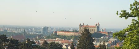 panorama photo of bratislava city, castle in distance, photo taken from slavin, hot air balloons in thy sky photo