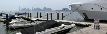 anchoring: several small boats and one big yacht anchoring in a manhattan port, jersey city in background Stock Photo