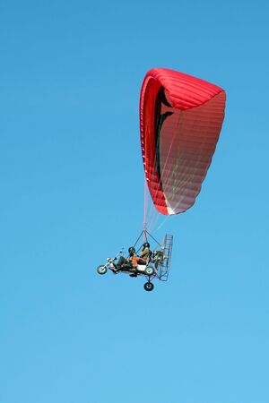 dual: trike dual paragliding on red wing, clear blue sky