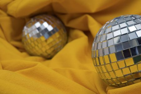 two disco balls on yellow background, shallow depth of view photo