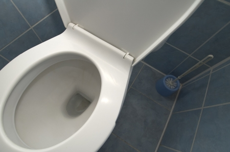 public waste: white clean toilet detail photo, blue tiled floor and walls