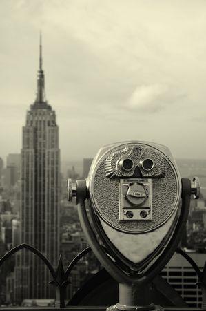 black and white manhattan photo, steel binoculars in foreground, empire state in background