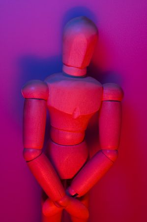 conceptual photo of a wooden figure, red and blue mixed lights, shy expression