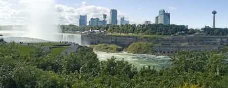 Horseshoe falls viewed from american side, Canadian Niagara falls city behind the river photo