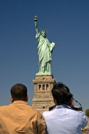 The Statue of Liberty in New York city, two man in foreground