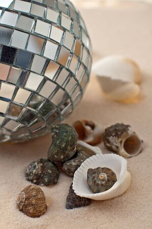party-ball and sea-shells on sand, vertical photo photo