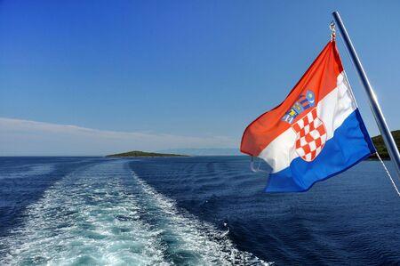 croatian: Croatian flag waving behind a passenger ship, water trail