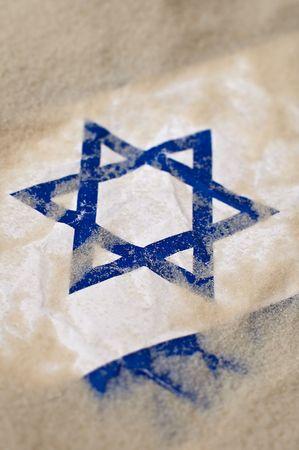 israeli: Foto de detalle de un burried de bandera de insreal en la arena, estrella de david en foco