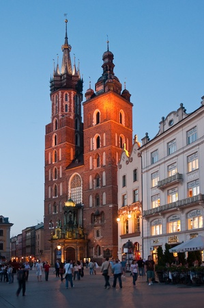 mary's: Saint Marys church in Krakow, Poland - built in 16th century, dominates the Old Town Square. Night vertical photo with people.