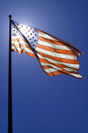 waving american flag, clear blue sky, sun is directly behind the flag Stock Photo