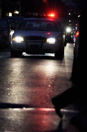 polizist: Polizei-Auto mit Lichtern auf, geht ein Mann Weg davor, Nachtszene Lizenzfreie Bilder