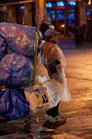 31. Mars 2011 - Manhattan, New York, Etats-Unis - une femme d'�ge moyen en imperm�able avec un chariot plein de canettes collect�es. Photo prise � Manhattan, New York, Etats-Unis, le 31. mois de mars. 2011. Editeur