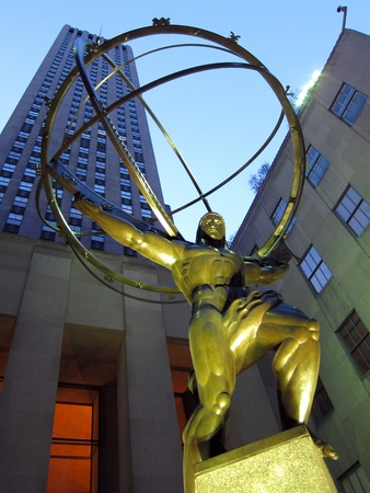 titan: The GE Building behind the Atlas Statue at Rockefeller Center on 5th Avenue in New York City.