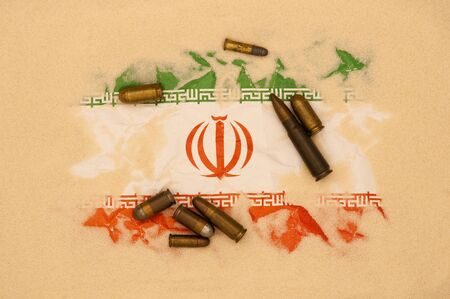 terrorism: Iran flag covered in sand with different ammunition scatter on it