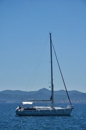 anchoring: abandoned yacht anchoring in calm waters, coastline in background, vertical photo,