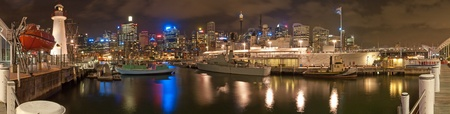 Darling Harbour in Sydney, night panorama photo with HMAS battleship and other boats from Maritime museum.