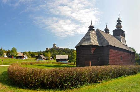 openair: wooden church in an open-air museum (slovak: skanzen) in Stara Lubovna, Slovakia. Castle on hill in background.