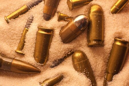 riffle: several different gun and riffle bullets lying in sand