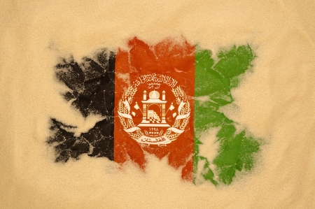 afghanistan: wrinkled Afghanistan flag buried in sand