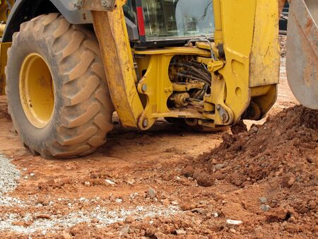 yellow excavator detail photo, brown soil photo