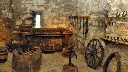 medieval blacksmith: museum exposition of an blacksmith workshop in a castle. panorama photo