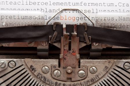 communicate concept: word blog and other text written on an old typewriter