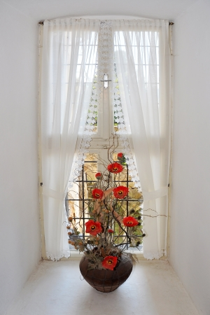 artificial flowers: flowerpot with artificial flowers on white window frame, historical building Stock Photo