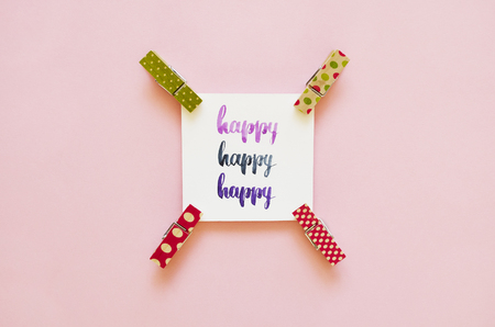 Happy handwritten with watercolor in calligraphy style, miniature clothespins on a pink background. Flat lay, top view.