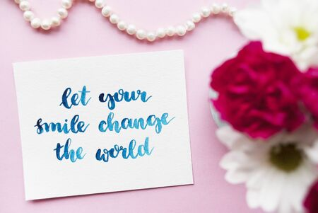 Inspirational quote Let your smile change the world written in calligraphy style with watercolor. Composition on a pink background. Flat lay.