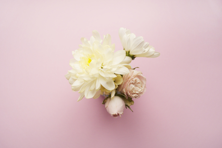 Bouquet of white chrysanthemums and cream roses on a pink background. Flat lay Stock Photo