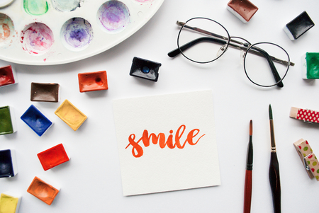 Artist workspace. Word Smile written in calligraphy style, watercolor cuvettes and palette on a white background Foto de archivo