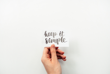 Minimal composition on a white background with girl's hand holding card with inspirational quote