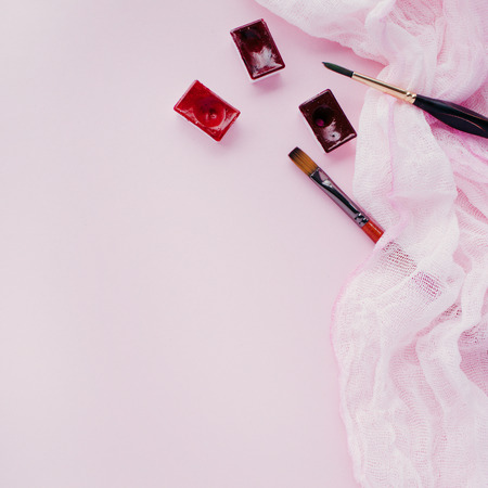 Minimal composition with paint brushes, watercolor cuvettes, lightweight cloth on a pink pastel background Foto de archivo
