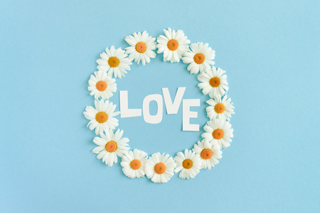 Word Love made of letters cut out of paper. Wreath made of white chamomile on a blue pastel background Stockfoto