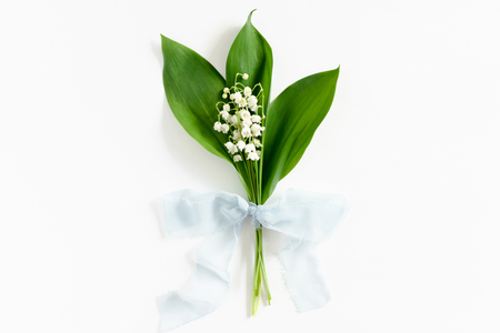 Bouquet of lilies of the valley with green leaves tied with a ribbon on a white background Banque d'images